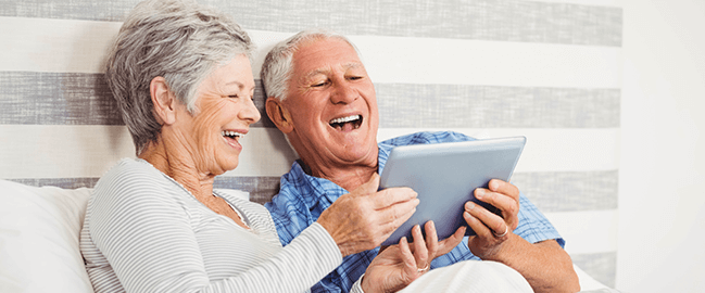 senior couple laughing at tablet screen