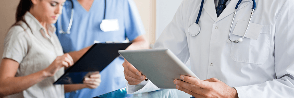 doctor looking at tablet with two nurses reviewing a chart in background