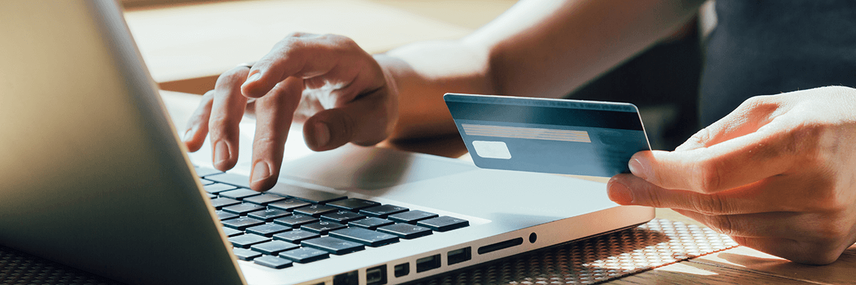 Person typing into laptop while holding a credit card