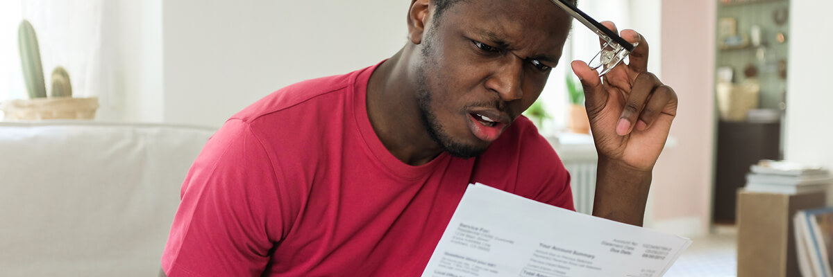 Man looking surprised while reading a bill.