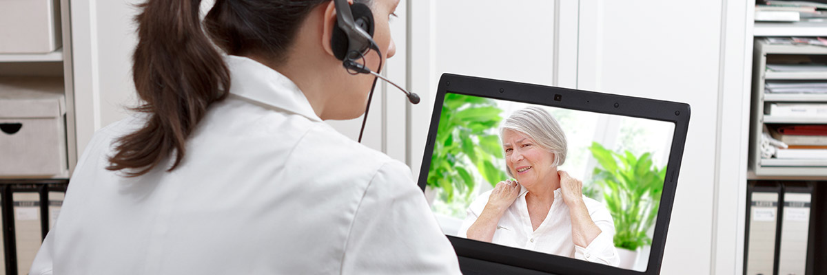 Doctor conducting telehealth visit with elderly woman