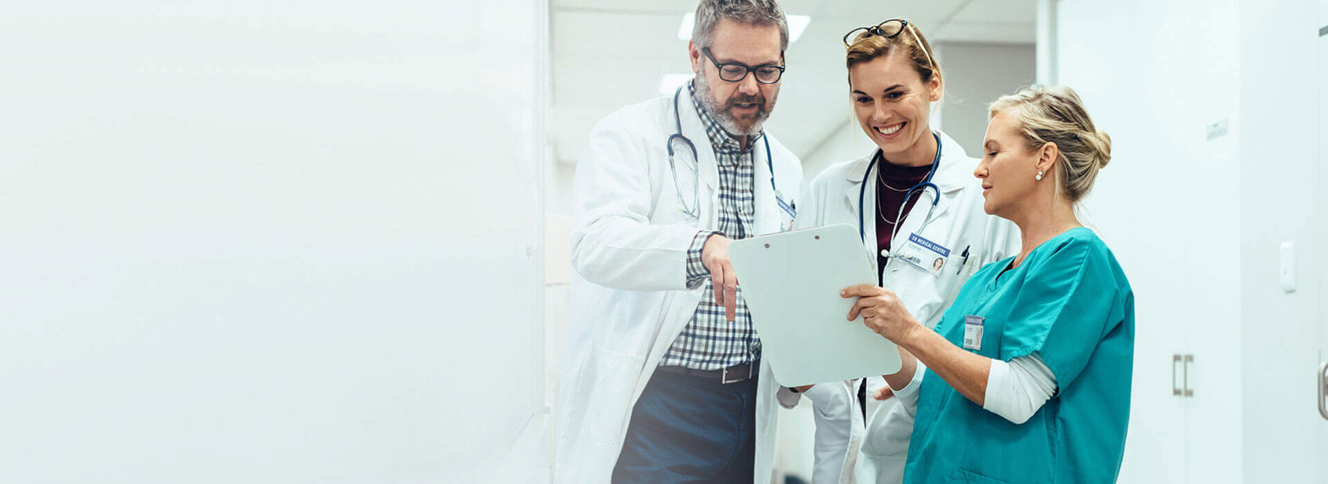 Physicians and nurse collaborate, reviewing patient notes before discharge